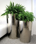 Hammered stainless steel conical planter.